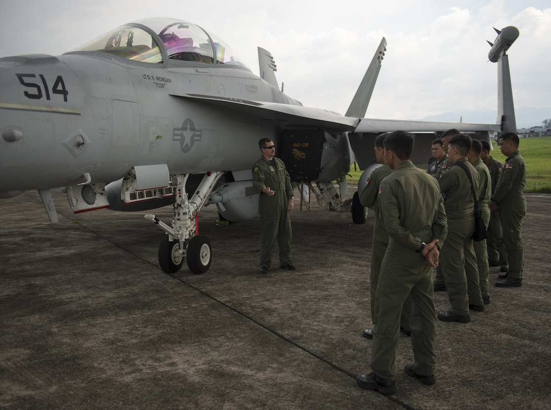U.S. Navy LCDR Jeff Pinkerton, an EA-18G Grolwer pilot assigned to Electronic Attack Squadron 138, speaks with a group of Philippine Air Force pilots assigned to Clark Air Base, Philippines, June 28, 2016. U.S. forces arrived in the Philippines to excercise bilaterally with the Armed Forces of the Philippines and support routine operational missions that enhance regional maritime domain awareness. (U.S. Air Force photo by Capt. Elias Zani/released)
