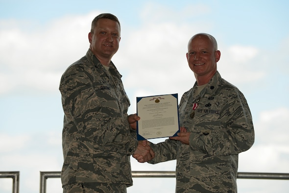 U.S. Air Force Col. Aeneas Gooding, the 509th Mission Support Group commander, presents the Meritorious Service Award to Lt. Col. Jeffery Carter, the outgoing 509th Security Forces Squadron (SFS) commander, at Whiteman Air Force Base, Mo., July 6, 2016. Carter relinquished command of the 509th SFS to Maj. Justin Secrest. (U.S. Air Force photo by Senior Airman Sandra Marrero)