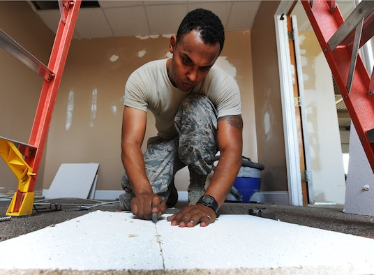 U.S. Air Force Staff Sgt. William Shelden, a 509th Civil Engineer Squadron structural journeyman, cuts a new ceiling tile at Whiteman Air Force Base, Mo., July 5, 2016. A building that was previously unoccupied is now being renovated to host the Airman's Attic. (U.S. Air Force photo by Airman 1st Class Michaela R. Slanchik)