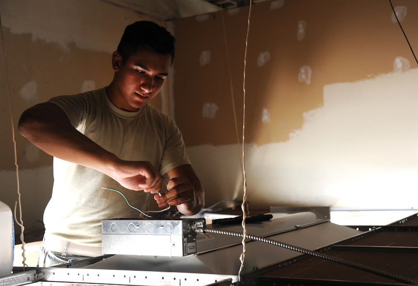 U.S. Air Force Airman 1st Class Farid Dom, a 509th Civil Engineer Squadron electrical systems apprentice, installs a light at the new Airman's Attic at Whiteman Air Force Base, Mo., July 5, 2016. The Airman's Attic accepts clothing and household good donations, which are offered for free to Airmen E-5 and below. (U.S. Air Force photo by Airman 1st Class Michaela R. Slanchik)