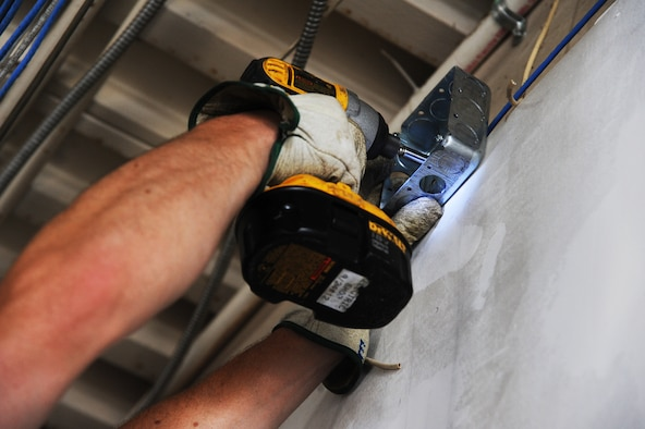 U.S. Air Force Senior Airman Eric Miller, a 509th Civil Engineer Squadron electrical systems journeyman, mounts a four-inch square outlet box to the wall of the new Airman's Attic at Whiteman Air Force Base, Mo., July 5, 2016. The Airman's Attic is scheduled to open at its new location on August 19, 2016. (U.S. Air Force photo by Airman 1st Class Michaela R. Slanchik)