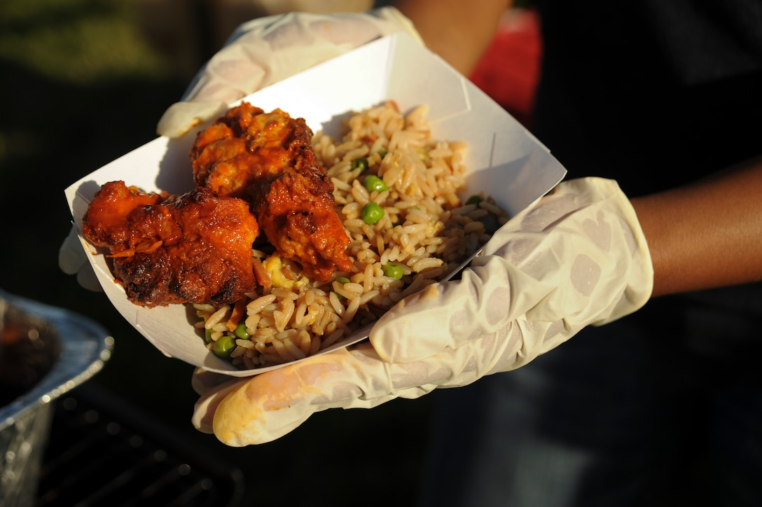 A 131st Medical Group member holds up a half order of buffalo and honey barbecue chicken wings with fried rice served at their tent during the Independence Day Celebration at Whiteman Air Force Base, Mo., June 30, 2016. The food and drinks were part of the celebration held at Ike Skelton Lake for Whiteman personnel and their families. (U.S. Air Force photo by Senior Airman Danielle Quilla)