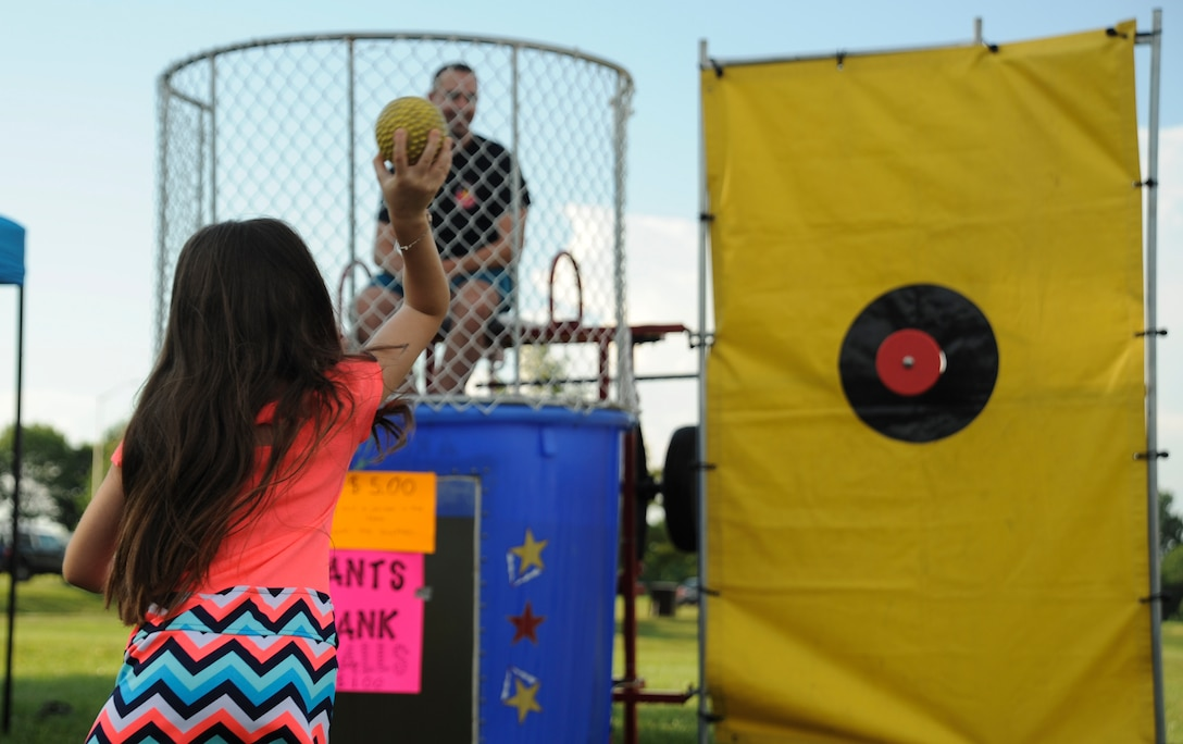 A participant of the Independence Day Celebration throws a ball toward the dunk tank button at Whiteman Air Force Base, Mo., June 30, 2016. Personnel and their families had the opportunity to send their squadrons' first sergeants into the tank of cold water. (U.S. Air Force photo by Senior Airman Danielle Quilla)