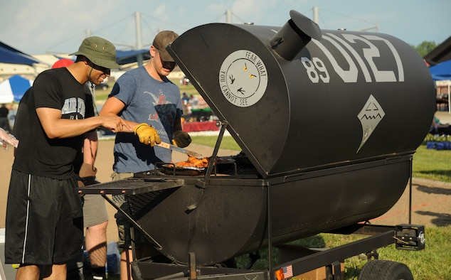U.S. Air Force Senior Airman Christian Anthony, left, and Senior Airman Brandon Orourke, right, 509th Maintenance Squadron members, grill chicken wings during the Independence Day Celebration at Whiteman Air Force Base, Mo., June 30, 2016. Squadrons participated in the event by selling refreshments or supervising activities for Team Whiteman. (U.S. Air Force photo by Senior Airman Danielle Quilla)