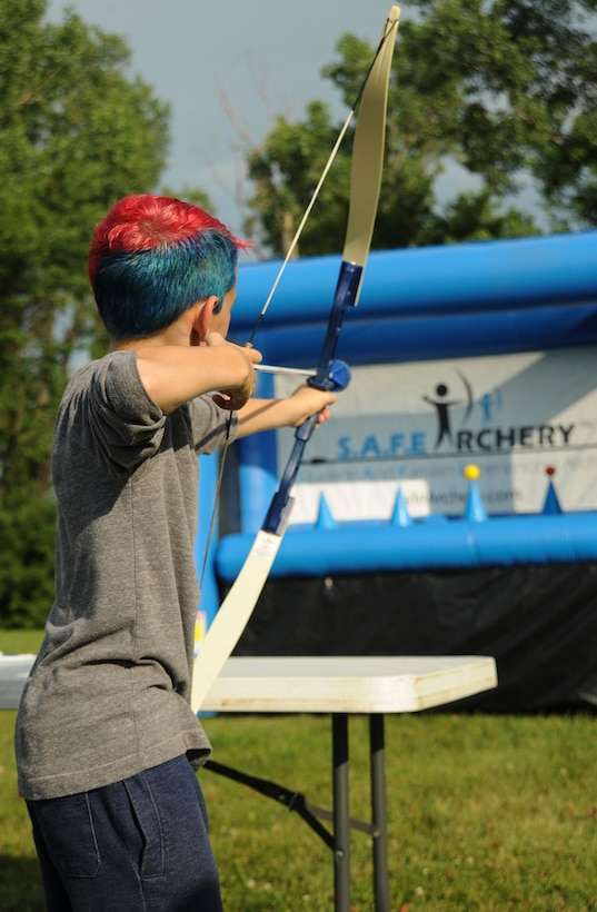 A participant of the Independence Day Celebration aims an arrow at a hover ball inflatable target at Whiteman Air Force Base, Mo., June 30, 2016. In addition to the inflatable activities, the event also included live music, a zip line, refreshments, and a face-painting and balloon station prior to an evening of fireworks. (U.S. Air Force photo by Senior Airman Danielle Quilla)