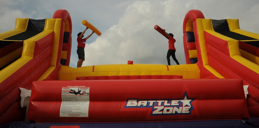 U.S. Air Force Brig. Gen. Paul W. Tibbets IV, the 509th Bomb Wing (BW) commander, left, and Chief Master Sgt. Melvina Smith, 509th BW command chief, right, prepare to spar on the inflatable jousting challenge during the Independence Day Celebration at Whiteman Air Force Base, Mo., June 30, 2016. More than 10 inflatable activities and a zip line were available to guests at the event. (U.S. Air Force photo by Senior Airman Danielle Quilla)