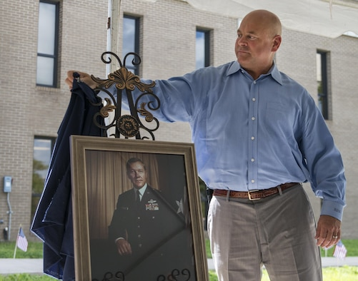 Brian Haugen, the son of retired Brig. Gen. Donald Haugen, unveils the portrait of his father at the 919th Special Operations Wing headquarters building dedication ceremony at Duke Field, Fla., July 8.  The building was dedicated to the 919th's founding member, Haugen, who created the 919th Tactical Airlift Group in 1971.  The portrait will be hung in the newly-named Haugen Headquarters.  (U.S. Air Force photo/Tech. Sgt. Sam King)