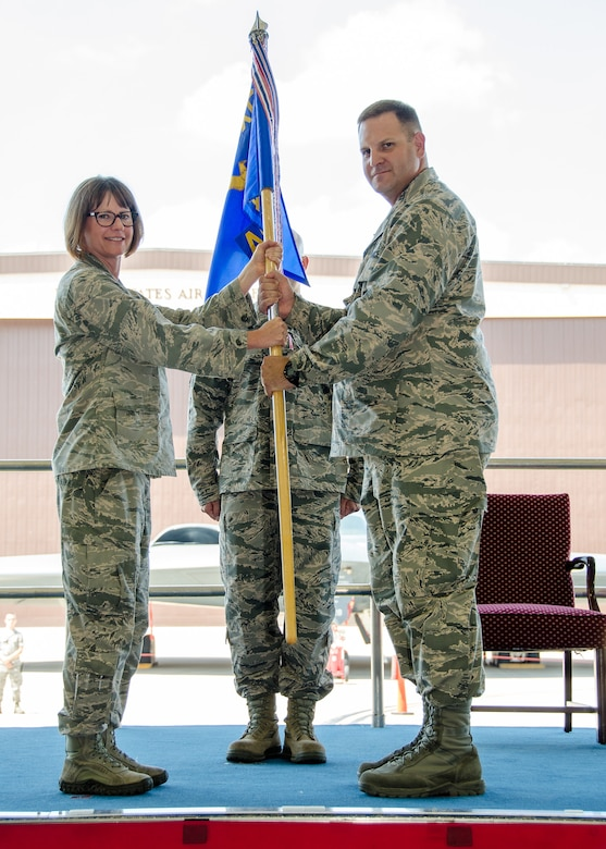 Lt. Col. Michael Belardo, the new 131st Aircraft Maintenance Squadron commander, takes the guidon from Col. Kimbra Sterr, commander of the 131st Maintenance Group during a change of command ceremony during the Missouri Air National Guard's 131st Bomb Wing July drill weekend at Whiteman Air Force Base, Missouri. Belardo, previously the director of operations for the 509th Operations Support Squadron, is replacing outgoing squadron commander Lt. Col. Matthew Calhoun, who will serve as the new 131st BW vice commander. (U.S. Air National Guard photo by Airman 1st Class Halley Burgess)
