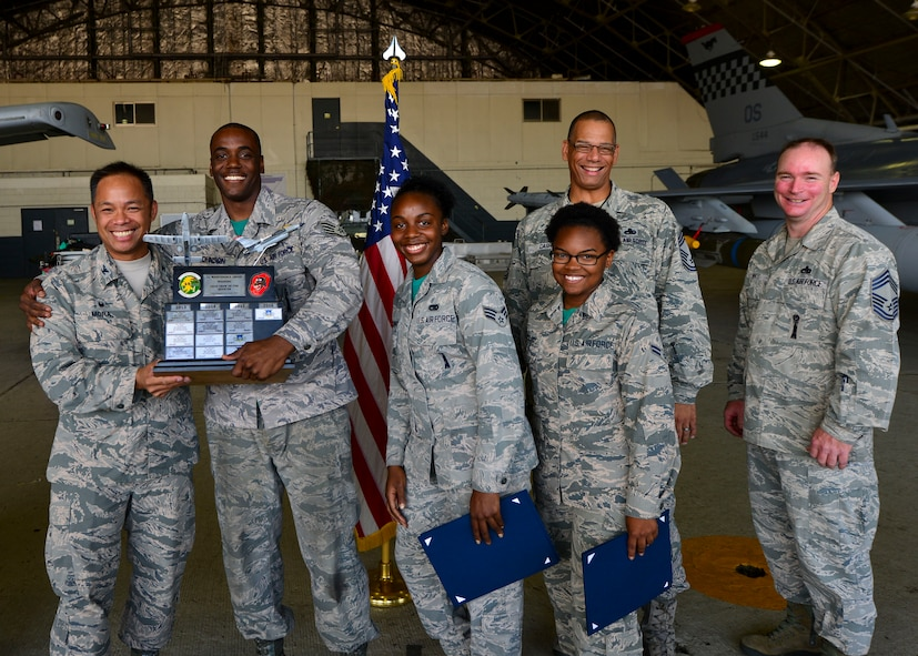Staff Sgt. Michael Johnson, Senior Airman Mel-Neiqua Montgomery, and Airman 1st Class Saravia Boykins, pose with 51st Maintenance Group leadership after winning the quarterly weapons load crew competition at Osan Air Base, Republic of Korea, July 7, 2016. The best weapons load crews from the 36th and 25th Aircraft Maintenance Units competed to see who could arm their aircraft quickest and with the most precision. Johnson is a 25th AMU weapons load crew team chief, and Montgomery and Boykins are 25th AMU weapons load crew members. (U.S. Air Force photo by Senior Airman Victor J. Caputo/Released)