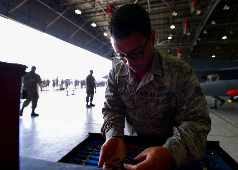 Senior Airman Jeremy Alvarez, 25th Aircraft Maintenance Unit weapons load crew member, looks for a specific item in a toolset at Osan Air Base, Republic of Korea, July 7, 2016. Alvarez was part of the 36th AMU weapons load crew competing for the 51st Maintenance Group Weapons Load Crew of the Quarter award. The teams were judged on dress and appearance in addition to their job skill and ability. (U.S. Air Force photo by Senior Airman Victor J. Caputo/Released)