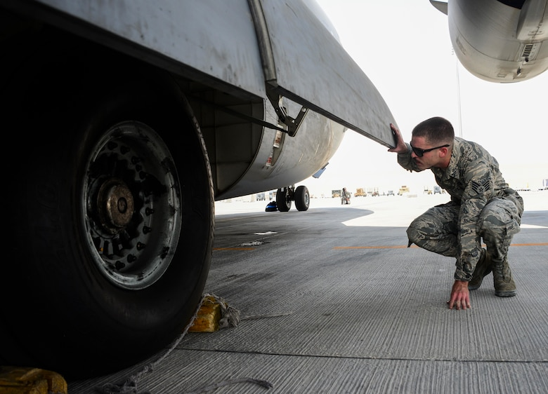 Staff Sgt. Josh Budinich, 8th Expeditionary Air Mobility Squadron, Aircraft Maintenance flight aero repair craftsman, inspects the tires of a C-17 Globemaster III during a preflight inspection June 30, 2016, at Al Udeid Air Base, Qatar. Budinich takes approximately three hours to inspect the whole aircraft, inside and out, from its tires and brakes to the oil in its engines. Due to the warm weather here, Airmen keep the aircraft at a constant temperature while operating on any of the systems on the aircraft to prevent additional issues from occurring. (U.S. Air Force photo/Senior Airman Janelle Patiño/Released)