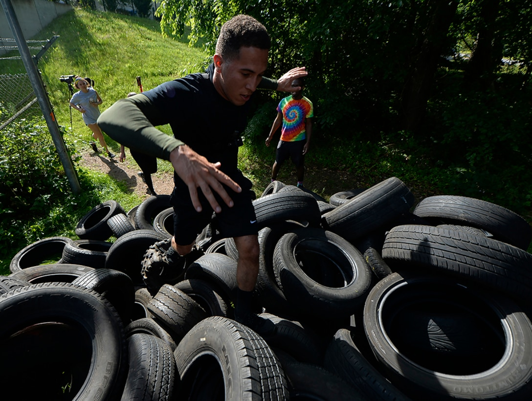 Senior Airman Corinthian Maldonado, 86th Airlift Wing commander executive administrator, climbs a hill of tires at the Mudless Mudder on Ramstein Air Base, Germany, July 8, 2016. More than 550 participants competed in the five-kilometer obstacle course for the 86th AW Resiliency Day. (U.S. Air Force photo/ Senior Airman Nesha Humes)