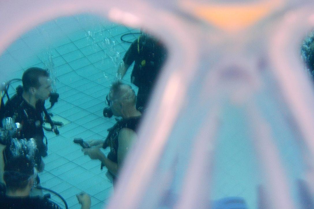 Erhard Bauman, Ramstein Aquatic Center's Professional Association of Diving Instructors Open Water Certification instructor, teaches students during hands-on training July 7, 2016, at Ramstein Air Base, Germany. The course is offered monthly for $475, which includes all gear and course material. It consists of four days classroom and hands-on training and two days in open water at a lake. (U.S. Air Force photo/Airman 1st Class Tryphena Mayhugh)