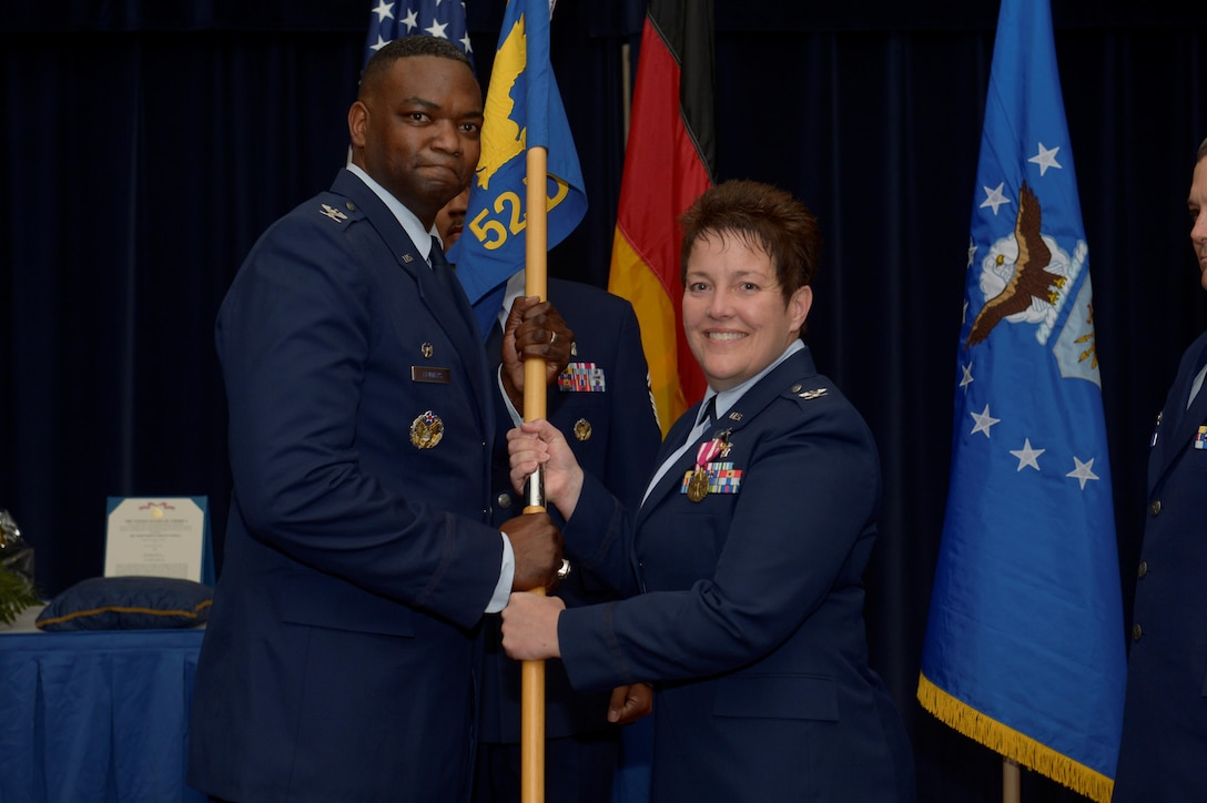 U.S. Air Force Col. Alfred Flowers, 52nd Medical Group commander, left, takes the ceremonial guidon from U.S. Air Force Col. Ann Blake, outgoing 52nd Dental Squadron commander, during the 52nd DS change of command ceremony on Spangdahlem Air Base, Germany, July 11, 2016. The guidon symbolized the authority Flowers placed on Blake, who then relinquished command over the 52nd DS as the flag exchanged hands. (U.S. Air Force photo by Staff Sgt. Jonathan Snyder/Released)