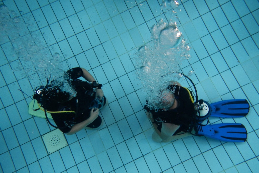 Erhard Bauman, Ramstein Aquatic Center's Professional Association of Diving Instructors open water certification instructor, teaches a student during hands-on training July 7, 2016, at Ramstein Air Base, Germany. The course includes four days of classroom and hands-on application in a pool and two days in open water at a lake. (U.S. Air Force photo/Airman 1st Class Tryphena Mayhugh)
