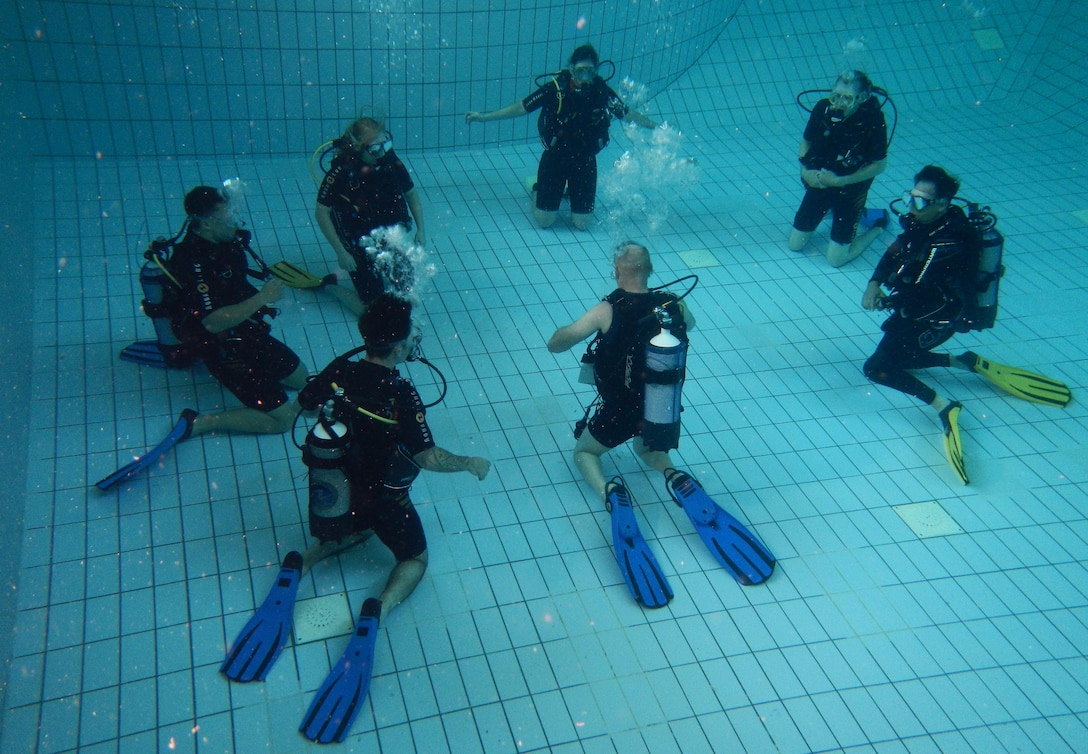 Erhard Bauman, Ramstein Aquatic Center's Professional Association of Diving Instructors open water certification instructor, teaches students during hands-on training July 7, 2016, at Ramstein Air Base, Germany. The course includes four days of classroom and hands-on application in a pool and two days in open water at a lake. (U.S. Air Force photo/Airman 1st Class Tryphena Mayhugh)
