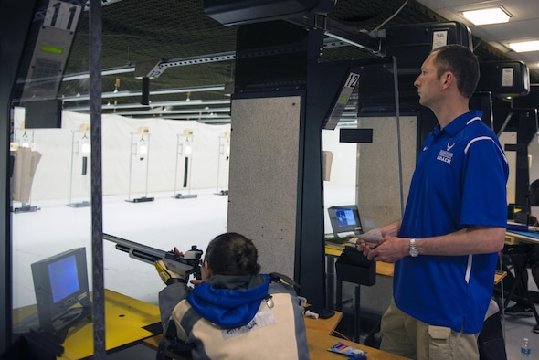 U.S. Air Force Maj. Robert Davis, 93d Air Ground Operations Wing director of complaints resolution, watches as athlete, retired Capt. Amanda Frey, shoots her Walther LG400 .177 caliber air rifle while practicing for the 2016 Department of Defense Warrior Games shooting competition June 18, 2016, at the United States Military Academy in West Point, N.Y. Frey credits the efforts of Davis and the Air Force Wounded Warrior Program for motivating her throughout her recovery and rehabilitation process. (U.S. Air Force photo by Airman 1st Class Greg Nash/Released)