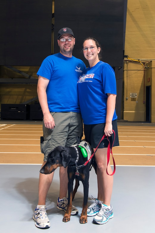 Retired U.S. Air Force Capt. Amanda Frey, right, her husband, Capt. Jason Frey, 4th Special Operations Squadron AC-130U aircraft commander, and their dog Orion, pose for a photo during the 2016 Department of Defense Warrior Games at the United States Military Academy in West Point, N.Y. After sustaining a traumatic brain injury from a convoy rollover in Iraq in 2010, Amanda joined the Air Force Wounded Warrior Program's shooting team during her recovery and rehabilitation efforts. (U.S. Air Force photo by Airman 1st Class Greg Nash/Released)
