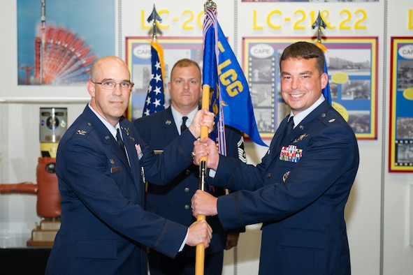 Col. Steven Lang, 45th Launch Group commander, presents Lt. Col. Waylon Mitchell, 5th Space Launch Squadron commander, with a guidon during a change of command ceremony July 7, 2016, at Cape Canaveral Air Force Station, Fla. Changes of command are a military tradition representing the transfer of responsibilities from the presiding official to the upcoming official. (U.S. Air Force photo/Benjamin Thacker/Released)