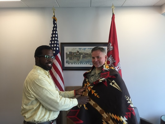 Rodney Parker, Huntington District Tribal Liaison presenting Col Philip Secrist with a Shawnee Blanket.