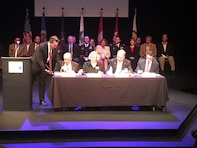 FARGO, N.D. -- Darrell Vanyo, Diversion Authority chairman, from left; Del Rae Williams, Moorhead, Minnesota, mayor; Tim Mahoney, Fargo, North Dakota, mayor; and Lowry Crook, Principal Deputy Assistant Secretary of the Army (Civil Works), sign a project partnership agreement in Fargo, July 11.  The project partnership agreement signing initiates the construction phase of the U.S. Army Corps of Engineers' Fargo-Moorhead Metropolitan Area Flood Risk Management Project. This project includes building a 30-mile diversion channel that will direct floodwater around the Fargo-Moorhead metropolitan area. The project will reduce flood risk for more than 225,000 people and 70 square miles of infrastructure.