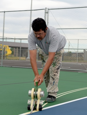 Ruben Reyes, Renner Sports Surfaces foreman, outlines painting areas for the multi-purpose sport courts at Ellsworth Air Force Base, S.D., June 14, 2016. The court can be used for different activities including tennis, basketball and volleyball, each requiring its own set of lines. (U.S. Air Force photo by Airman Donald Knechtel/Released)