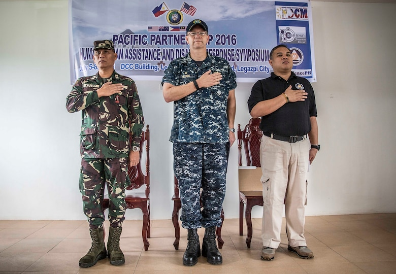 Philippine Air Force Brig. Gen. Claudio L. Yucot (left), U.S. Navy Capt. Tom Williams, mission commander, Pacific Partnership 2016 (center), and Director Bernardo R. Alejandro IV, regional director, Office of Civil Defense 5, render honors during the Philippine national anthem at the start of a Humanitarian Assistance Disaster Relief workshop in support of Pacific Partnership 2016. During the three-day workshop, co-hosted by the Armed Forces of the Philippines and Pacific Partnership 2016, Filipino civilians and military service members coordinated a tabletop exercise to simulate multilateral disaster response among partners during a crisis. Pacific Partnership is visiting the Philippines for the seventh time since its first visit in 2006. Partner nations are working side-by-side with local military and non-government organizations to conduct cooperative health engagements, community relation events and subject matter expert exchanges to better prepare for a natural disaster or crisis.