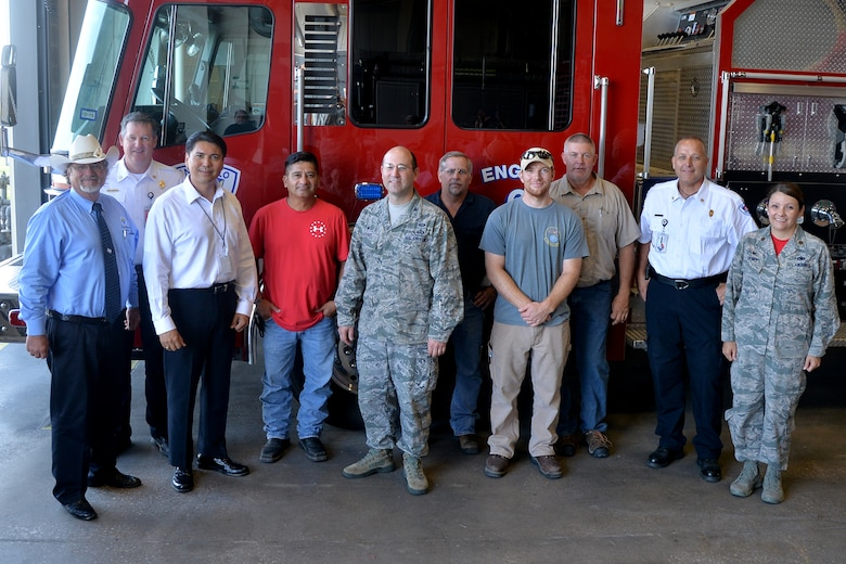Goodfellow Air Force Base and the City of San Angelo members stand beside one of San Angelo Fire Department's fire trucks on Goodfellow Air Force Base, Texas, July 8, 2016. In exchange for maintaining fire trucks, the City of San Angelo will provide ambulance services to the base. (U.S. Air Force photo by Airman 1st Class Randall Moose/Released)