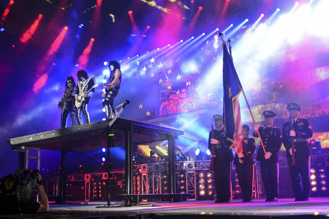 """Members of the Oregon Army National Guard display the American flag on stage while the band Kiss performs the national anthem during the """"Freedom to Rock"""" concert in Eugene, Ore., July 9, 2016. The soldiers provided a color guard for the band's patriotic tribute to U.S. military and veterans at the concert. Oregon National Guard photo by Maj. W. Chris Clyne"""