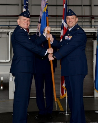 U.S. Air Force Col. Thomas Torkelson, left, 100th Air Refueling Wing commander, passes the guidon to U.S. Air Force Col. Robert Hoskins, right, new 100th Mission Support Group commander, June 29, 2016, during a change of command ceremony on RAF Mildenhall, England. The ceremony is a time-honored tradition in which one officer relinquishes command and passes it to another. (U.S. Air Force photo by Airman 1st Class Tenley Long/Released)