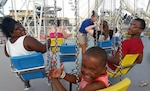 Malaysia, E.J. and Treyvon are ready to swing on the boardwalk in Wildwood, New Jersey during DLA Troop Support's Family Day July 7. Thousands of employees and their guests spent the day at water parks and on amusement rides during the annual gathering.