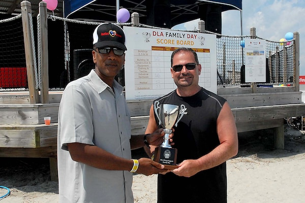 Army Brig. Gen. Charles Hamilton, DLA Troop Support commander (left), presents Anthony D'Ambrosio, Construction and Equipment deputy director, with the Family Day trophy after the supply chain gained the most points during a series of games, including volley ball, musical chairs and quizzo.