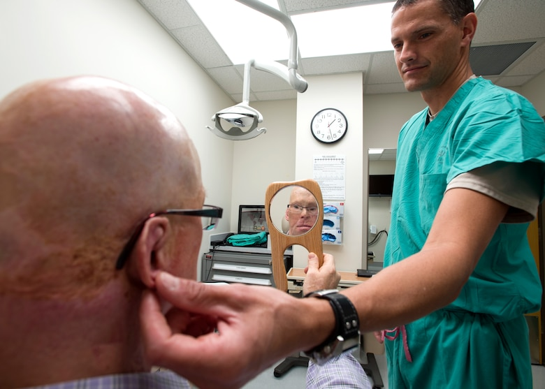 Maj. Stephen Cherrington (right), 59th Dental Group maxillofacial prosthodontist, checks the fitting of retired Army Master Sgt. Todd Nelson's prosthetic ear at the San Antonio Military Medical Center, Joint Base San Antonio-Fort Sam Houston, Texas, June 28. The 59th Medical Wing's Maxillofacial Prosthetics Department is one of only a few in the Department of Defense that creates prosthetic body parts, such as eyes, ears and noses. (U.S. Air Force photo/Staff Sgt. Kevin Iinuma)