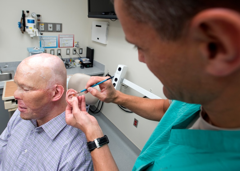 Maj. Stephen Cherrington (right), 59th Dental Group maxillofacial prosthodontist, colors retired Army Master Sgt. Todd Nelson's new prosthetic ear to match his skin tone at the San Antonio Military Medical Center, Joint Base San Antonio-Fort Sam Houston, Texas, June 28. (U.S. Air Force photo/Staff Sgt. Kevin Iinuma)