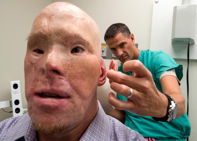Maj. Stephen Cherrington (right), 59th Dental Group maxillofacial prosthodontist, compares retired Army Master Sgt. Todd Nelson's new prosthetic ear to his skin tone at the San Antonio Military Medical Center, Joint Base San Antonio-Fort Sam Houston, Texas, June 28. (U.S. Air Force photo/Staff Sgt. Kevin Iinuma)