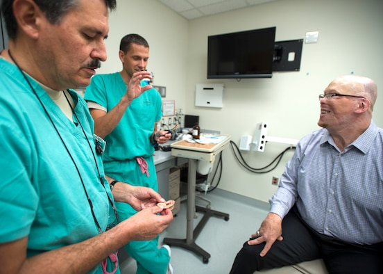 Col. Jose Villalobos (left), 59th Dental Group maxillofacial prosthetics program director, and Maj. Stephen Cherrington (center), 59th Dental Group maxillofacial prosthodontist, discuss retired Army Master Sgt. Todd Nelson's new prosthetic ear at the San Antonio Military Medical Center, Joint Base San Antonio-Fort Sam Houston, Texas, June 28. The 59th Medical Wing's Maxillofacial Prosthetics Department is one of only a few in the Department of Defense that creates prosthetic body parts, such as eyes, ears and noses. (U.S. Air Force photo/Staff Sgt. Kevin Iinuma)