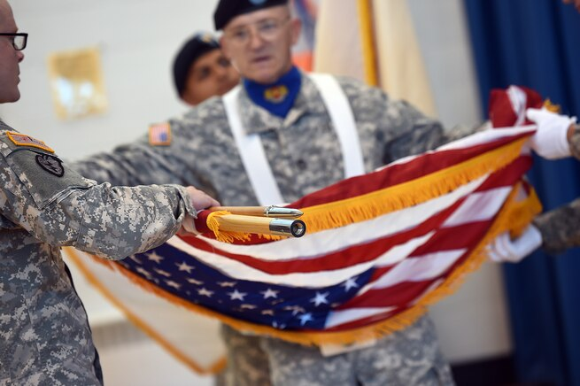 Members of the 85th Support Command color guard team roll up the American flag for safe keeping and transportation after the 2nd Mobilization Support Group, 85th Support Command's change of command ceremony in Arlington Heights on July 9, 2016. For a majority of the members on the team, this event was their first time participating.