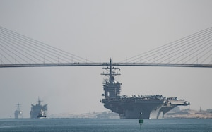 (July 8, 2016) The aircraft carrier USS Dwight D. Eisenhower (CVN 69), followed by the fast combat support ship USNS Arctic (T-AOE 8) and the guided-missile destroyer USS Nitze (DDG 94), passes under the Freedom Bridge while transiting the Suez Canal. The Eisenhower Carrier Strike Group is deployed in support of maritime security operations and theater security cooperation efforts in the U.S. 5th Fleet area of operations.