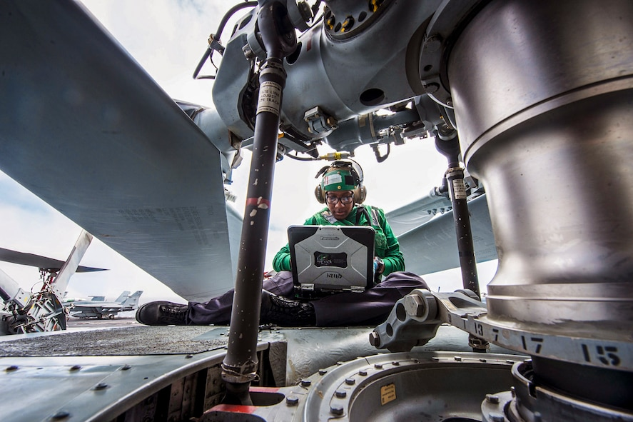Navy Seaman Janeih Bain performs maintenance on the rotor hub of an MH-60R Seahawk helicopter.