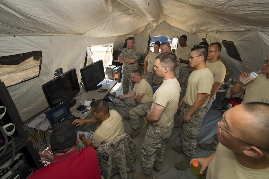 Members of Air Force Reserve squadrons gather as video teleconference equipment is set up during the Air Force Reserve Command Joint Incident Site Communications Capability (JISCC) exercise, July 12, 2016, Niagara Falls Air Reserve Station, N.Y. The exercise is meant to simulate how units would deploy anywhere in the U.S. to enable inter-agency communication during a man-made or natural disaster. (U.S. Air Force photo by Tech. Sgt. Stephanie Sawyer)