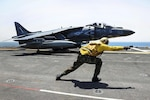 Navy Petty Officer 3rd Class Chase Coker launches an AV-8B Harrier II off the flight deck of amphibious assault ship USS Boxer in the Arabian Gulf, July 11, 2106. The Boxer is supporting Operation Inherent Resolve in the 5th Fleet area of operations. Coker is an aviation boatswain's mate handling. Navy photo by Petty Officer 2nd Class Jose Jaen