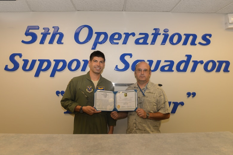 "Capt. Alex Kroll and Mr. Robert Seekings, 5th Operations Support Squadron Weapons System Trainer Mission Planning Cell team members, accept the 5th Bomb Wing ""Own It Award"" at Minot Air Force Base, N.D., July 12, 2016. Kroll and Seekings were awarded for recognizing a critical MPC gap in Secret Internet Protocol Router Network capability and creating a stand-alone MPC function. Kroll and Seekings coordinated with the 5th Communications Squadron and the 5th Civil Engineer Squadron to provide over $20,000 of foundational infrastructure to create this function. (U.S. Air Force Photo/Airman 1st Class Jessica Weissman)"