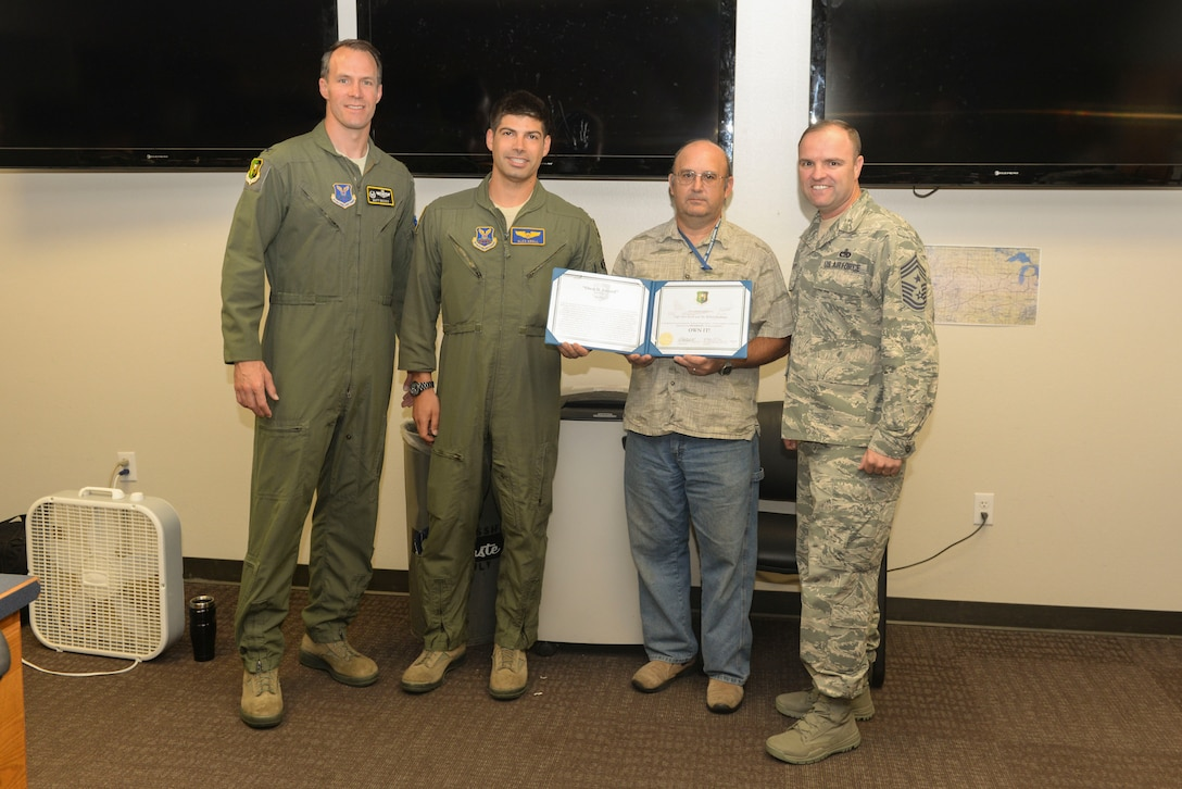 Col. Matthew Brooks, 5th Bomb Wing commander, left, and Chief Master Sgt. Paul Elliott III, 5th BW command chief, right, present an Own-It Award to Capt. Alex Kroll and Mr. Robert Seekings, 5th Operations Support Squadron Weapons System Trainer Mission Planning Cell (MPC) team members, at Minot Air Force Base, N.D., July 12, 2016. Kroll and Seekings were awarded for creating the first stand-alone MPC function. (U.S. Air Force photo/Airman 1st Class Jessica Weissman)