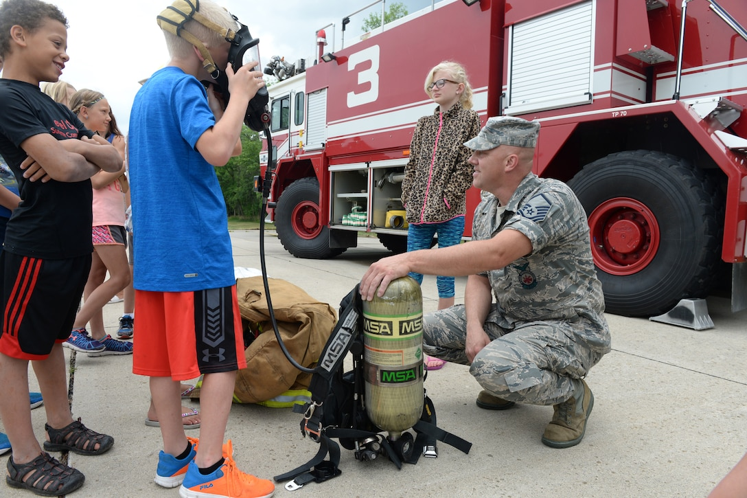 Master Sgt. Chad Noyes, a 119th Wing fire fighter, demonstrates equipment use for a group of children during a tour at the North Dakota Air National Guard Base, Fargo, North Dakota, July 7, 2016. (U.S. Air National Guard Photo by Senior Master Sgt. David H. Lipp/Released)