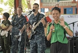 "160621-N-OU129-270 PATTAYA, Thailand (June 21, 2016) The U.S. Navy 7th Fleet Rock Band ""Orient Express"" invites a student from the Potisampan School to sing a local song during a joint rock concert with the Royal Thai Marine Corps Band in support of Cooperation Afloat Readiness and Training (CARAT) Thailand 2016 in Pattaya Thailand, June 21, 2016. CARAT is a series of annual maritime exercises between the U.S. Navy, U.S. Marine Corps and the armed forces of nine partner nations to include Bangladesh, Brunei, Cambodia, Indonesia, Malaysia, the Philippines, Singapore, Thailand, and Timor-Leste. (U.S. Navy photo by Mass Communication Specialist 2nd Class Joshua Fulton)"