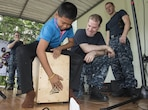 "160622-N-OU129-047 SATTAHIP, Thailand (June 22, 2016) The 7th Fleet Rock Band ""Orient Express"" teaches a student from Chuksamet School how to play a cajon box drum during a concert in support of Cooperation Afloat Readiness and Training (CARAT) Thailand 2016. CARAT is a series of annual maritime exercises between the U.S. Navy, U.S. Marine Corps and the armed forces of nine partner nations to include Bangladesh, Brunei, Cambodia, Indonesia, Malaysia, the Philippines, Singapore, Thailand, and Timor-Leste. (U.S. Navy photo by Mass Communication Specialist 2nd Class Joshua Fulton/Released)"