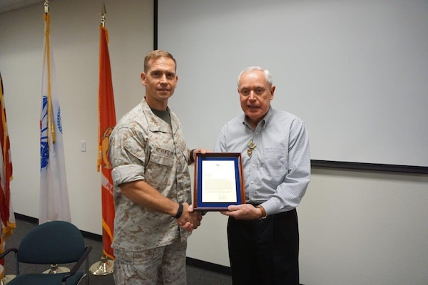 Paul Balash III, right, receives the DLA Exceptional Civilian Service Award from former DLA Distribution San Joaquin, Calif., commander Marine Col. Keith Reventlow prior to retiring.