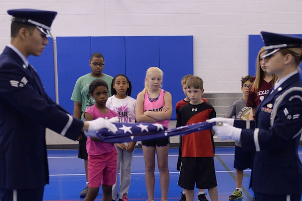 Military children watch Airmen from the base Honor Guard fold the flag during Youth Boot Camp at Minot Air Force Base, N.D., July 7, 2016. Children learned about drill, basic combatives, team-building and survival training during the week-long camp. (U.S. Air Force photo/Airman 1st Class Jessica Weissman)