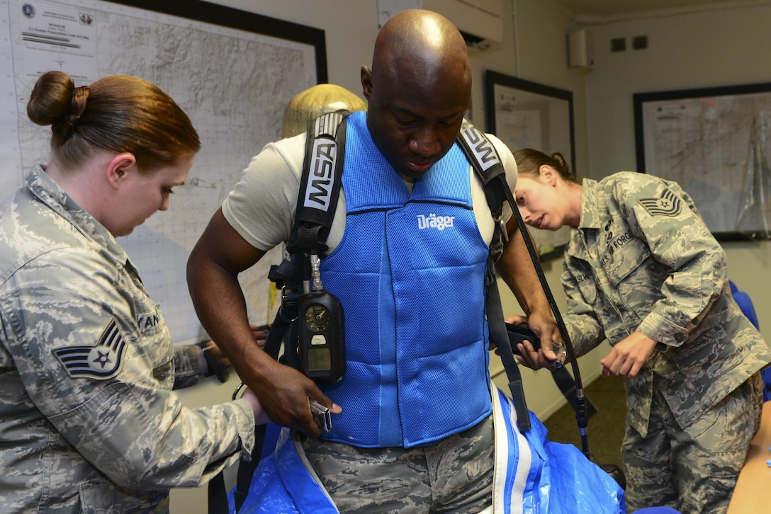 U.S. Air Force Staff Sgt. Lauren Yancey, 39th Civil Engineer Squadron (CES) emergency management journeyman, (left) and Tech. Sgt. Evelyn Nicholson, 39th CES emergency management craftsman, assist Chief Master Sgt. Vegas Clark, 39th Air Base Wing command chief, put on a Level A emergency management suit July 13, 2016, at Incirlik Air Base, Turkey. Clark prepared for a quick response scenario as part of Out Connecting with Airmen with the 39th CES readiness and emergency management flight. (U.S. Air Force photo by Tech. Sgt. Caleb Pierce)