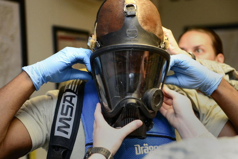 U.S. Air Force Chief Master Sgt. Vegas Clark, 39th Air Base Wing command chief, secures a Level A emergency management suit mask July 13, 2016, at Incirlik Air Base, Turkey. Clark received hands on experience of what the 39th Civil Engineer Squadron readiness and emergency management Airmen bring to the mission. (U.S. Air Force photo by Tech. Sgt. Caleb Pierce)